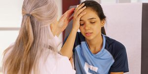 photograph of a girl in a soccer uniform holding her head due to a concussion while receiving concussion physiotherapy