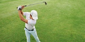photograph of an amateur golfer swinging a golf club with perfect form following the Fit-Fore Golf program