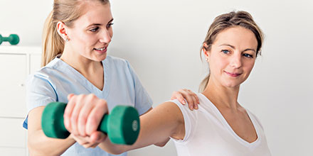 photograph of a physiotherapist helping a client improve strength and coordination following a spinal cord injury as part of Neurological rehabilitation