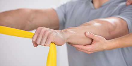 photograph of a male athlete performing strengthening arm exercises to maintain conditioning during sports injury rehabilitation